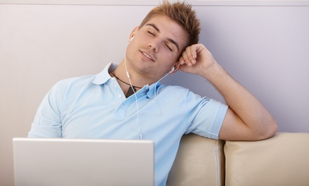 Portrait of boy daydreaming, listening to music with earphones on laptop computer, sitting on sofa with eyes closed. photo
