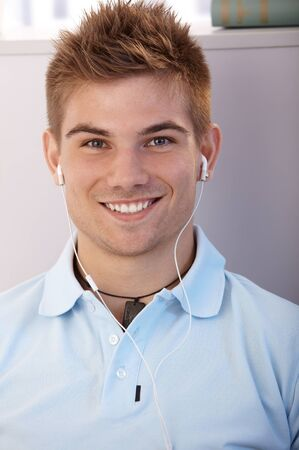 Portrait of happy goodlooking young guy smiling at camera with earphones. photo