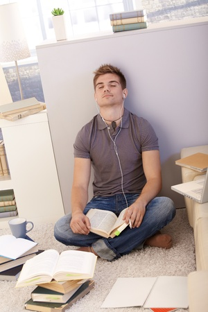 College student boy sitting on living room floor with books and notes, concentrating with eyes closed on studying with earphones. photo