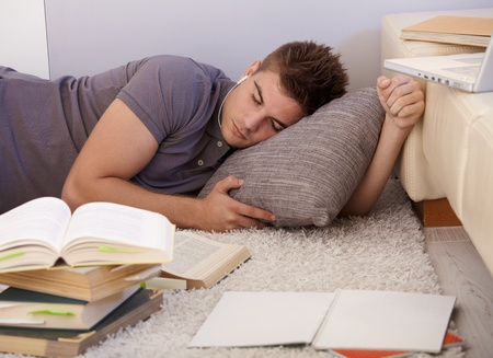 University student boy asleep on living room floor, surrounded by books and notes, exhausted from studying. Stock Photo - 12471071