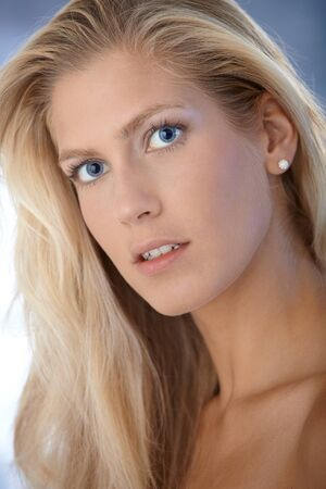 Closeup facial portrait of natural beauty with blonde hair and blue eyes, looking at camera. photo