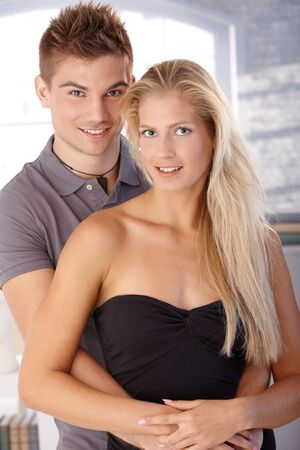 Portrait of beautiful smiling young couple standing, hugging, looking at camera. photo