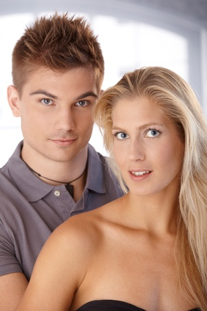 Closeup portrait of beautiful young couple looking at camera, smiling. photo