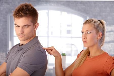 novios enojados: Novia enojada metiendo el hombro del novio con los dedos mirando malestar.