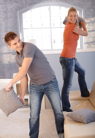 Attractive couple fighting with pillow in living room, laughing happily. photo