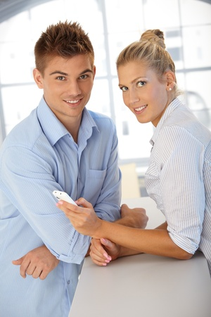 Happy couple standing together, smiling at camera, using mobile phone. Stock Photo - 12471033