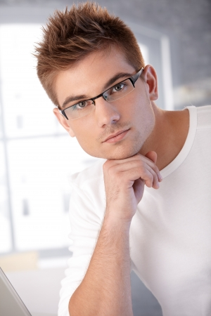 Portrait of trendy young man with fashionable hair style and glasses looking at camera. photo