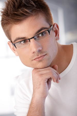 vertical image: Closeup portrait of stylish young handsome man thinking, wearing glasses.