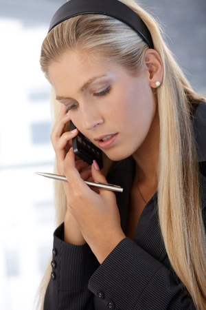 Businesswoman concentrating on mobile phone call, with pen handheld. photo