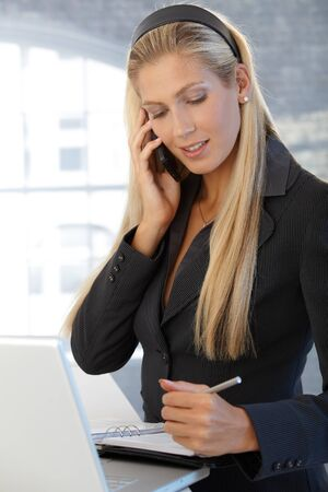 business woman phone: Smiling confident businesswoman writing notes into personal organizer, speaking on mobile phone, standing in office. Stock Photo