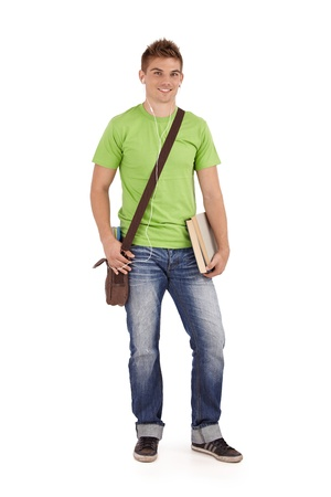 Smiling university student boy standing with books and bag, listening to music via earphones, white background. photo