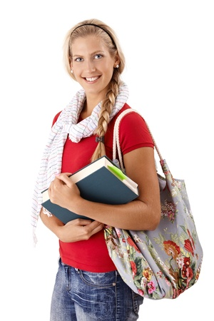 exercise book: Portrait of pretty university student girl in trendy clothes with book handheld, smiling at camera. Stock Photo