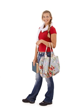 Trendy university student girl holding book and fashionable bag, smiling at camera, full length portrait. photo