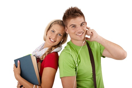 Happy college friends listening to music together, sharing earphones, holding book, smiling at camera. Stock Photo - 12470829