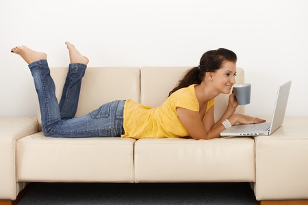lying on couch: Smiling young girl using laptop computer at home, laying on sofa.