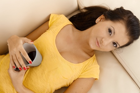 Young female resting on sofa, holding coffee cup, looking at camera, view from above. photo