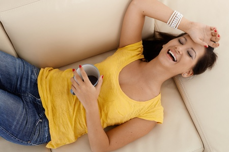Pretty girl laying on sofa at home, holding coffee cup, laughing. photo