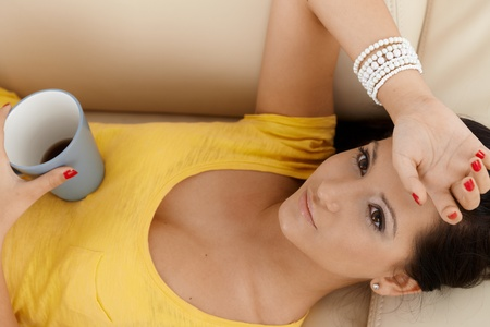 offish: Young female resting on sofa with coffee cup in hand, thinking. Stock Photo