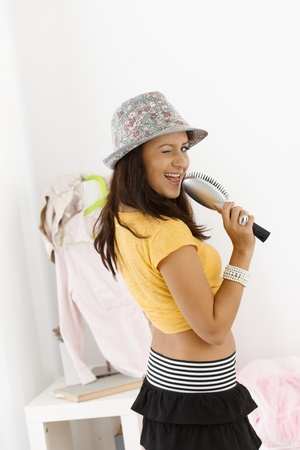 Young girl having fun at home, singing, smiling. photo