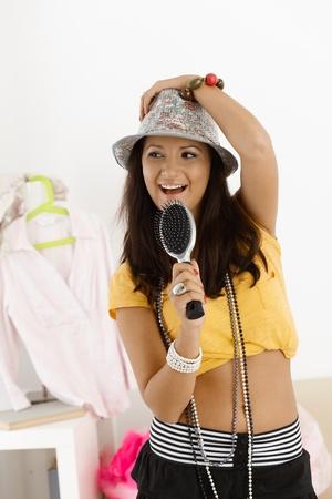 Teenage girl having fun at home, singing, posing. photo