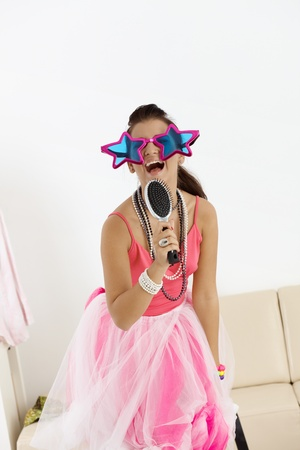funny glasses: Young girl singing at home in fancy-dress and funny glasses.