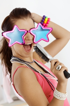 Teenage girl having fun at home, wearing funny glasses, singing to hairbrush. photo