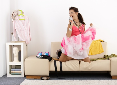 home accessories: Pretty teenage girl having fun at home, singing, posing, laughing.