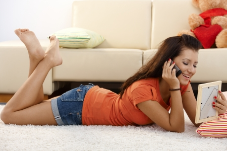 prone: Pretty young girl talking to boyfriend on mobile, laying on floor, looking at his photo.