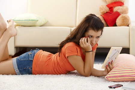 desperate face: Lovelorn young girl laying on floor at home, looking at ex-boyfriend photo.