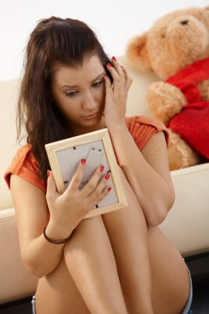 Heart-broken young girl looking at ex-boyfriends photo crying. photo