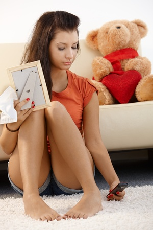 Lovelorn teenage girl sitting on floor at home, looking sad. photo
