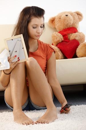 highschool: Lovelorn teenage girl sitting on floor at home, looking sad.