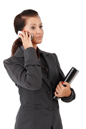 offish: Young businesswoman talking on mobile phone, holding personal organizer.