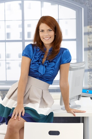 Pretty businesswoman posing in office, sitting on desk, smiling at camera. Stock Photo - 12471789