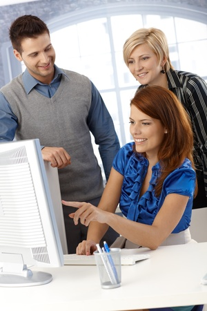 white color worker: Happy team looking at desktop computer screen, businesswoman pointing at screen, smiling.