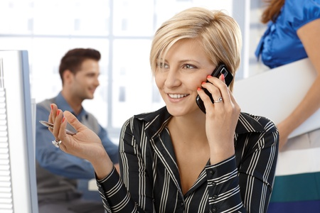 Happy businesswoman on phone call, smiling, gesturing with pen handheld, busy office in background. photo