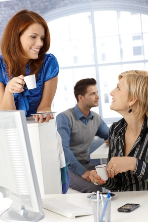 Coffee break in office, businesswomen chatting, holding coffee cup, smiling. photo