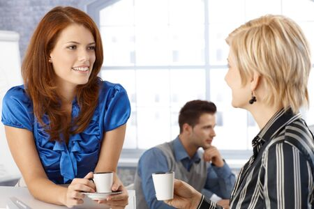 Businesswoman on coffee break, talking to colleague, smiling. photo