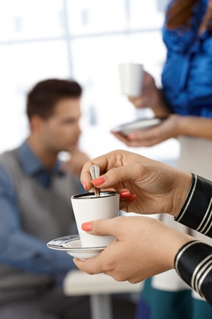 women holding cup: Having coffee in office, break time, closeup hands and coffee cup, selective focus.