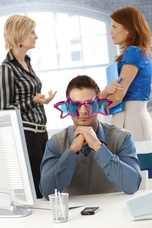 Businessman sitting at desk in funny colorful star shape glasses, daydreaming at work, having a break. photo