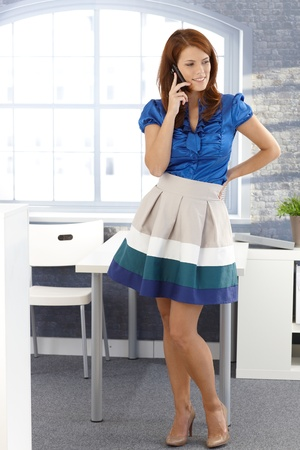 Attractive businesswoman using mobile phone, smiling, standing in office.