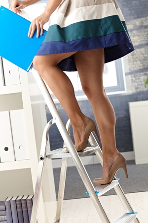 short: Pretty office assistant in short skirt standing on ladder, organizing file folder. Stock Photo