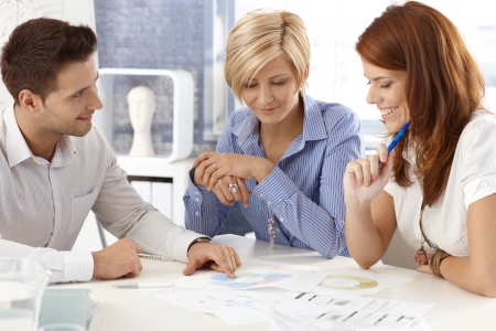 Portrait of happy businessteam working together a meeting table, businessman explaining, pointing at documents. photo