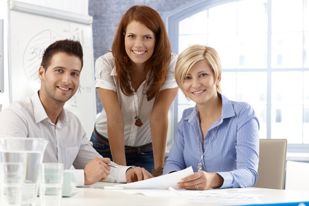 stockphoto: Portrait of happy and attractive office team, smiling at camera.