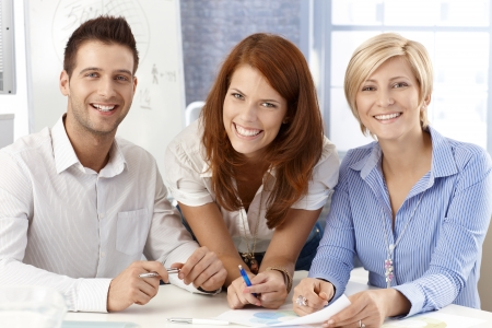 co worker: Laughing business team posing in office, smiling at camera. Stock Photo