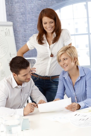 Cheerful office team busy at work, checking documents in meeting room. Stock Photo - 12471878