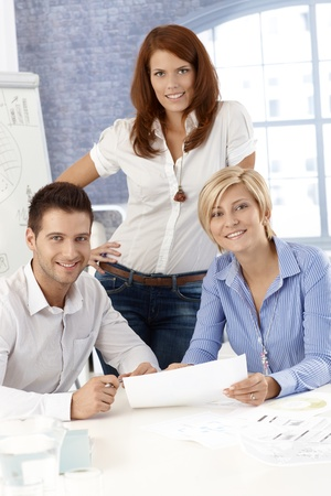 vertical image: Portrait of active office team working together, smiling confidently.