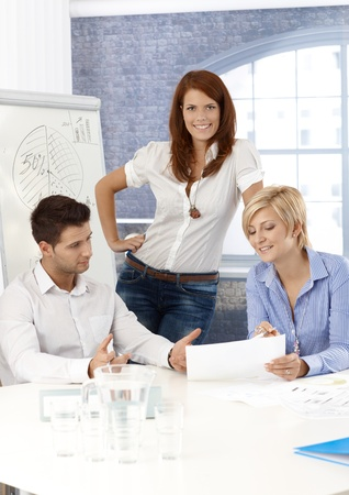 vertical image: Businessteam in meeting room, working on project together, smiling.