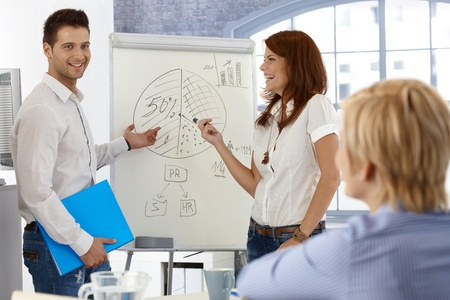 demo: Happy businesspeople working with whiteboard, doing presentation, using diagram. Stock Photo