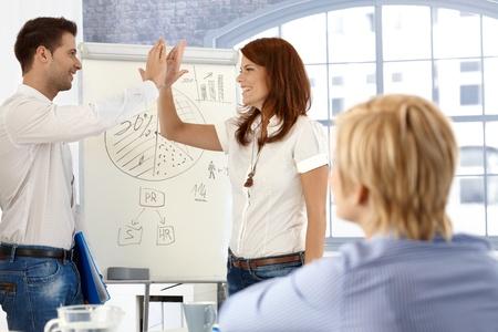 jovenes emprendedores: Los empresarios haciendo chocar los cinco, despu�s de la exitosa presentaci�n en la sala de reuniones. Foto de archivo